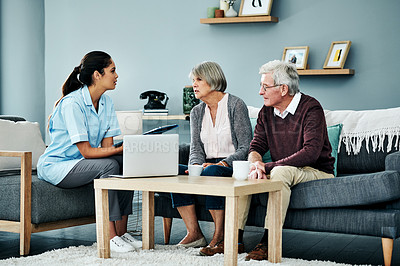 Buy stock photo Shot of a young nurse having a discussion with a senior couple