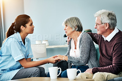 Buy stock photo Shot of a young nurse holding hands with a senior woman while sitting next to her husband