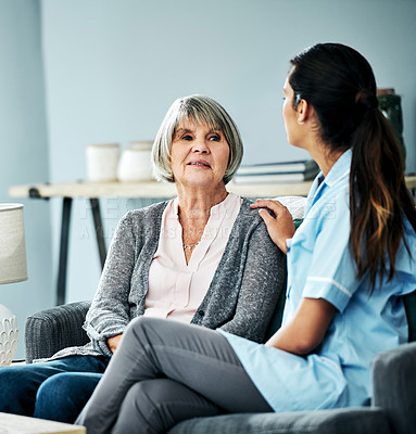 Buy stock photo Shot of a young nurse chatting with a senior woman at home