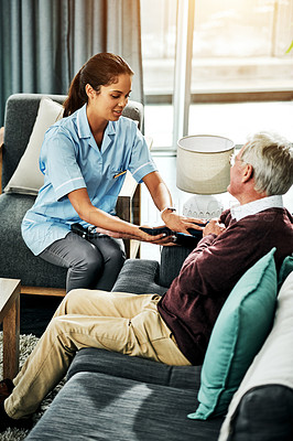 Buy stock photo Shot of a senior man getting his blood pressure measured during a checkup with a young nurse