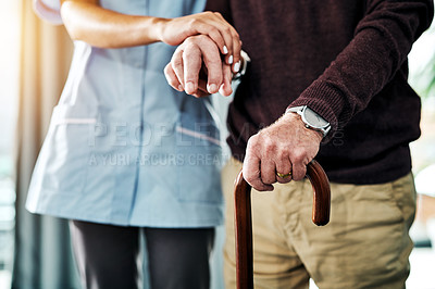 Buy stock photo Shot of a young nurse assisting a senior man who's walking with a cane
