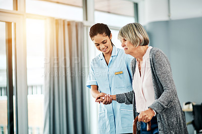 Buy stock photo Shot of a female nurse assisting a senior woman who's walking with a cane