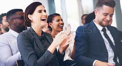 Buy stock photo Cropped shot of an attractive young businesswoman sitting with her colleagues and clapping while in the office during the day