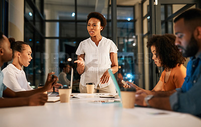 Buy stock photo Shot of a group of businesspeople having a meeting in a boardroom at night