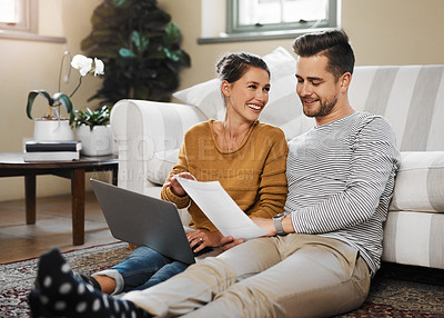Buy stock photo Shot of a couple looking at a document while using their laptop