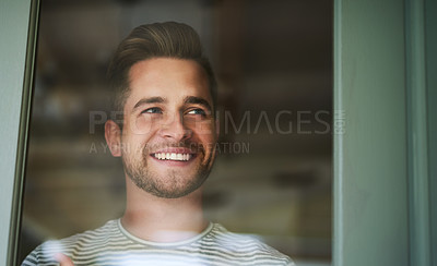 Buy stock photo Shot of a handsome young man looking out of a window at home and smiling