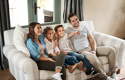 Buy stock photo Shot of a happy young family relaxing on the sofa and watching tv together at home