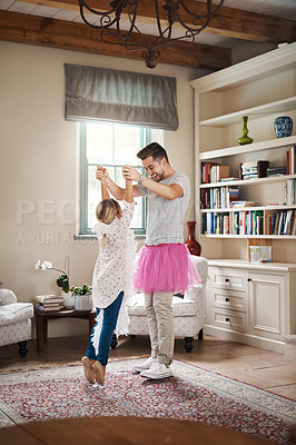 Buy stock photo Shot of a happy father and daughter dancing together at home