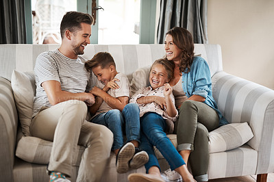 Buy stock photo Shot of a happy young family of four playing together on the sofa at home