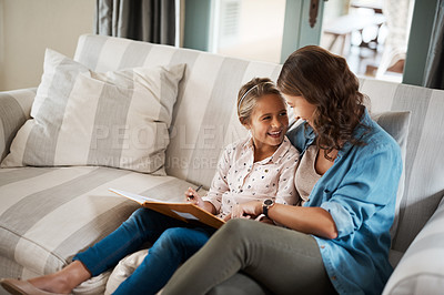 Buy stock photo Shot of a young woman helping her adorable daughter with her homework at home