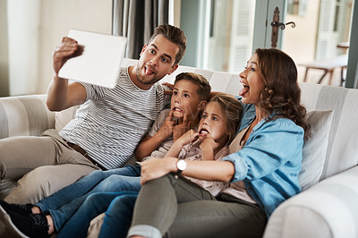 Buy stock photo Shot of a young family of four taking selfies together with a digital tablet on the sofa at home