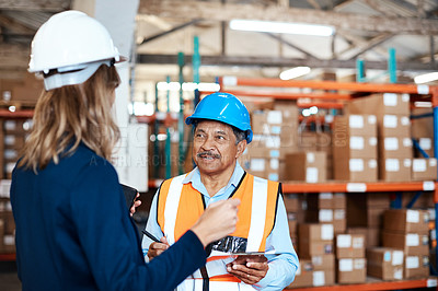 Buy stock photo Shot of a man and woman having a discussion while working together in a warehouse
