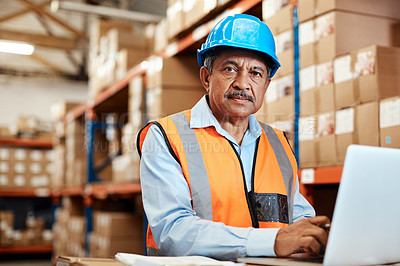 Buy stock photo Shot of a mature man using a laptop while working in a warehouse