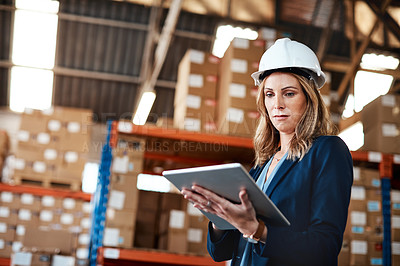 Buy stock photo Cropped shot of an attractive young businesswoman using a tablet while working in a warehouse