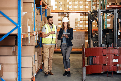 Buy stock photo Full length shot of an attractive young businesswoman walking through a warehouse with a male worker