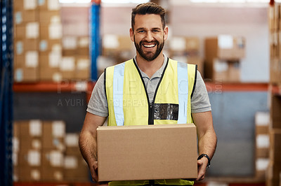 Buy stock photo Cropped portrait of a handsome young male warehouse worker carrying a box