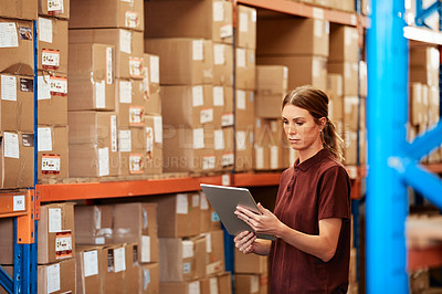 Buy stock photo Shot of a young woman using a digital tablet in a warehouse