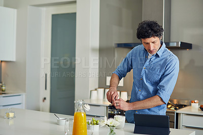 Buy stock photo Shot of a mature man using a digital tablet while making coffee at home in the morning.