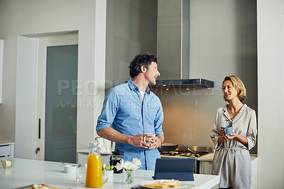 Buy stock photo Shot of a mature couple having coffee together in the kitchen at home