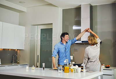 Buy stock photo Shot of a mature couple dancing while preparing breakfast in the kitchen at home