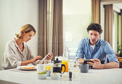 Buy stock photo Shot of a mature couple using digital tablets while having breakfast at home