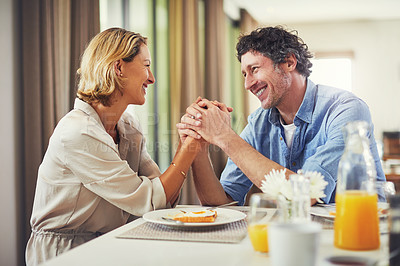 Buy stock photo Shot of a mature couple sharing romantic moment while having breakfast at home