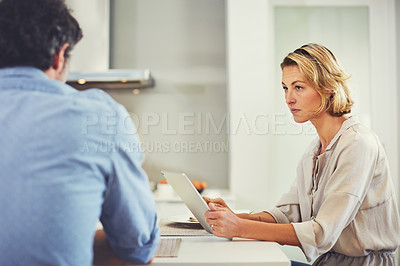 Buy stock photo Shot of a mature woman using a digital tablet while having breakfast with her husband at home