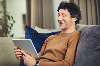 Buy stock photo Shot of a mature man using a digital tablet on the sofa at home