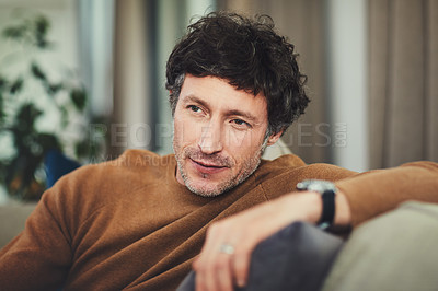 Buy stock photo Shot of a mature man looking thoughtful while relaxing on the sofa at home