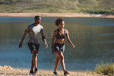 Buy stock photo Shot of two sporty young people walking back after their run