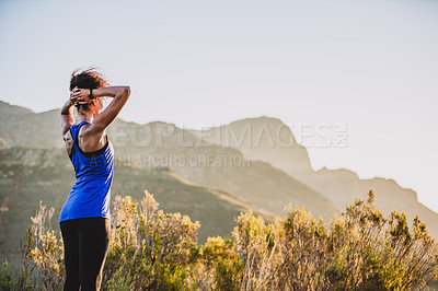 Buy stock photo Shot of a sporty young woman admiring the scenic view while out for a run