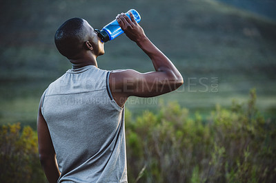 Buy stock photo Shot of a sporty young man drinking water while out for a run in nature