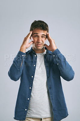 Buy stock photo Cropped shot of a man suffering from a headache against while posing against a grey background