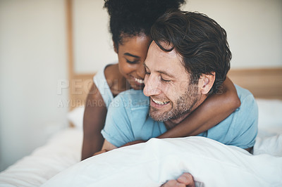 Buy stock photo Shot of an affectionate young couple sharing an intimate moment while relaxing on their bed at home