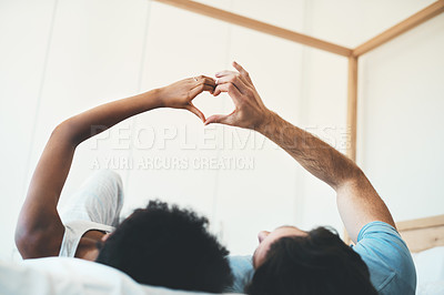 Buy stock photo Cropped shot of an unrecognizable affectionate young couple making a heart shape with their hands while lying on their bed at home