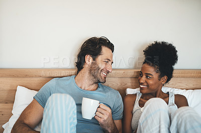 Buy stock photo Cropped shot of an affectionate young couple having coffee in their bedroom at home