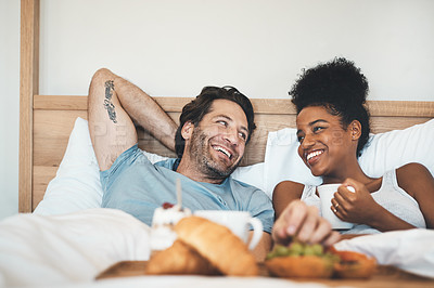 Buy stock photo Cropped shot of an affectionate young couple having their breakfast in bed at home
