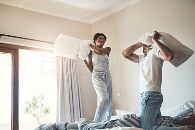 Buy stock photo Cropped shot of an affectionate young couple having a pillow fight in their bedroom at home
