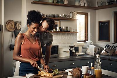 Buy stock photo Cropped shot of an affectionate middle aged man kissing his wife on the cheek while she prepares breakfast in their kitchen at home