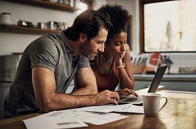 Buy stock photo Cropped shot of an affectionate young couple using a laptop while doing their budget paperwork in their kitchen at home