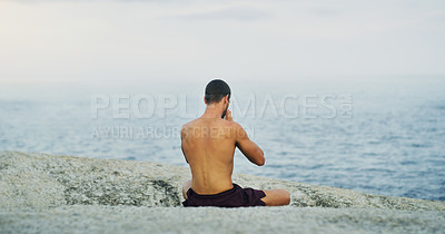 Buy stock photo Rearview shot of an unrecognizable man sitting cross legged and meditating alone by the ocean during an overcast day
