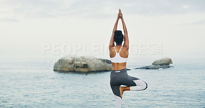 Buy stock photo Rearview shot of an unrecognizable woman standing and doing yoga alone by the ocean during an overcast day