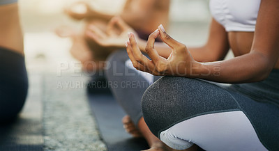 Buy stock photo Cropped shot of an unrecognizable group of people sitting and meditating together while on the beach during an overcast day