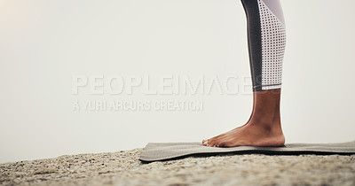 Buy stock photo Cropped shot of an unrecognizable person standing on a yoga mat while on the beach during an overcast day