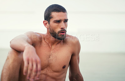 Buy stock photo Cropped shot of a handsome shirtless young sportsman taking a break after a workout outdoors