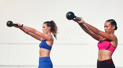 Buy stock photo Cropped shot of two attractive young sportswomen working out with kettle bells outdoors