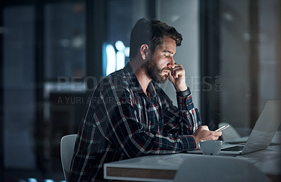 Buy stock photo Shot of a young businessman using a cellphone and laptop in an office at night