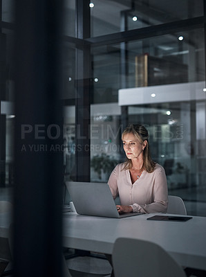 Buy stock photo Shot of a mature businesswoman working on a laptop in an office at night