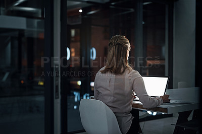 Buy stock photo Rearview shot of a mature businesswoman using a laptop while writing notes in an office at night