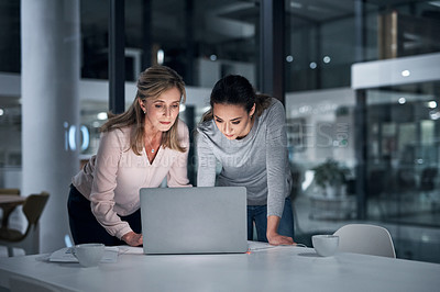 Buy stock photo Shot of two businesswomen working together on a laptop in an office at night